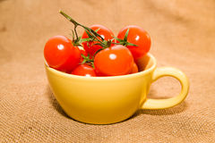Red cherry tomatoes in a yellow cup on old cloth Stock Photo