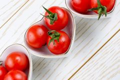 Red cherry tomatos in heart shaped bowl royalty free stock photo