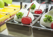 Red cherry topped on chocolate cup cake  with green leaf Stock Images