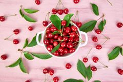 Red cherry in white bowl. On pink background. Summer or spring concept. Harvest. Some cherries near the bowl. Flat lay. Top view Stock Image