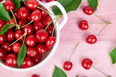 Red cherry in white bowl. On pink background. Summer or spring concept. Harvest. Some cherries near the bowl. Flat lay. Top view Royalty Free Stock Photography