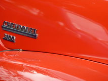 Red Chevrolet 3100 bonnet background. A Chevrolet 3100 bonnet and wing in bright red, with reflections from the sun Royalty Free Stock Image