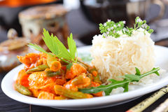 Red chicken curry stripes with rice. And vegetable royalty free stock photo