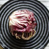 Red chicory on the black plate in the kitchen. Red and fresh chicory close up view Stock Photo