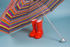 Red children rainboots and a colorful umbrella. Red children rain boots and a colorful umbrella stock images