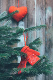 Red children`s mittens hanging on the branches of spruce and red plush heart on a wooden background. Tinted photo royalty free stock photography