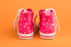 Red children& x27;s shoes. On orange background. stock photo