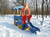 Red children's slide as a locomotive in the snow park area of ​​the city Stock Image