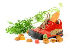 Red childrens shoe with carrot and pepernoten Stock Image