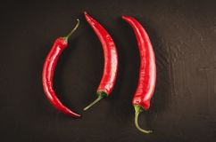 Red Chile pepper on a dark background/red hot Chile pepper on a dark stone background. Top view. Peppers chili black food slate chilly mexican natural fresh royalty free stock photography