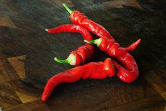 Red chile peppers on a wooden chopping board. Hot red chile peppers on a wooden chopping board Royalty Free Stock Photo