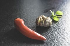 Red Chili Beside Brown Bead and Green Leaf Stock Images