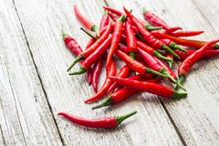 Red chili or chilli cayenne pepper on white wooden table.  stock images