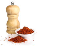 Red chili flakes. With grinder in the background isolated in whit Stock Images