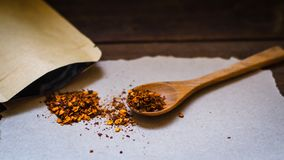 Red Chili flakes in wooden spoon on paper Asian food Thai food. Background royalty free stock photos