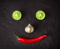 Red chili , garlic and lime lemon arrange as smiling face on bla Stock Images