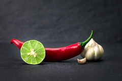 Red chili , garlic and lime lemon arrange on black stone backgro Stock Photo