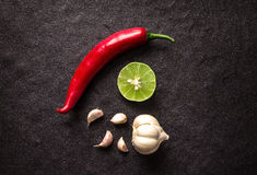 Red chili , garlic and lime lemon arrange on black stone backgro Royalty Free Stock Image