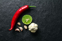 Red chili , garlic and lime lemon arrange on black stone backgro Royalty Free Stock Photos