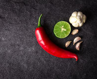 Red chili , garlic and lime lemon arrange on black stone backgro Royalty Free Stock Photo