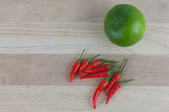 Red chili and lemon on wooden cutting board Royalty Free Stock Photos