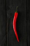 Red chili pepper on the black wooden background Royalty Free Stock Image