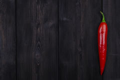 Red chili pepper on the dark wood background, close up Stock Image