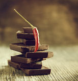 Red chili pepper on stack of dark chocolate pieces Royalty Free Stock Photo