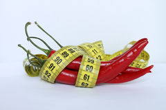 Red chili pepper. Tailors Tape. Measuring tape. Red chili pepper with measuring tape Royalty Free Stock Photo