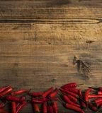 Red chili pepper on a vintage plate, dried chillies on wooden background. Top view. Copy spase. stock photo