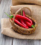 Red chili pepper in a wicker basket with burlap Stock Image