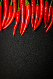 Red chili peppers on black background, Fresh hot chili peppers. Fresh spice ingredient for cooking Royalty Free Stock Images