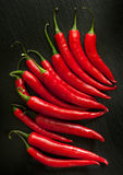 Red chili peppers on a black board Royalty Free Stock Photos