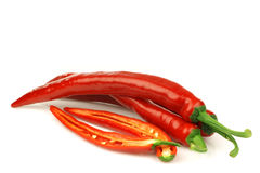 Red chili peppers (Capsicum) and a cut one Royalty Free Stock Image