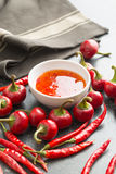 Red chili peppers and chili sauce. Red chili peppers and chili sauce on kitchen table Stock Photos