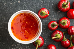 Red chili peppers and chili sauce. Royalty Free Stock Image