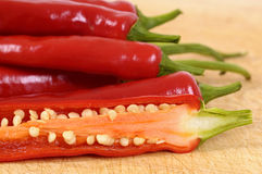 Red chili peppers cut half inside showing seeds close up Stock Photos