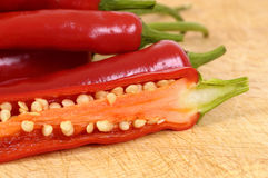 Red chili peppers cut half inside showing seeds Stock Photos
