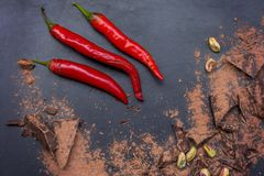 Red chili peppers and dark chocolate pieces. On black background Stock Photo