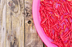 Red chili peppers drying in sun on wooden table Stock Image
