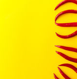 Red chili peppers. Red hot chili peppers on yellow background. Top view with copy space on the left Stock Photo