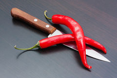 Red chili peppers and knife on the kitchen Stock Image
