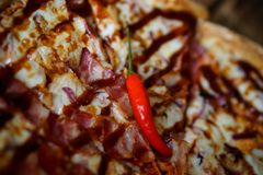 Red chili peppers are lying on a home-baked barbecue-pizza sauce. Daylight. Close-up stock photo