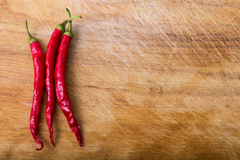Red chili peppers over wood. Red hot chili peppers over wood royalty free stock image