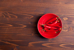 Red chili peppers in the plate on a dark wooden table top view o Stock Image