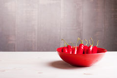 Red chili peppers in the plate on a light wooden table on the le Stock Images