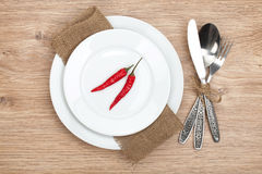 Red chili peppers on plate and silverware set Royalty Free Stock Photo