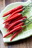 Red chili peppers on plate on wooden background Royalty Free Stock Photography