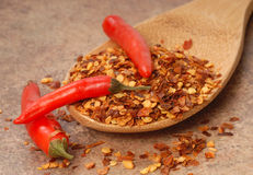 Red chili peppers and red pepper flakes on a spoon Royalty Free Stock Image