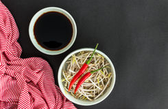 Red chili peppers on soybean sprouts, soy sauce in bowl and a st Stock Image